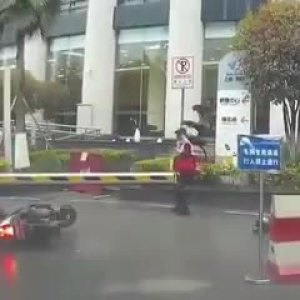 摩托车骑士被停车场护栏砍飞头盔